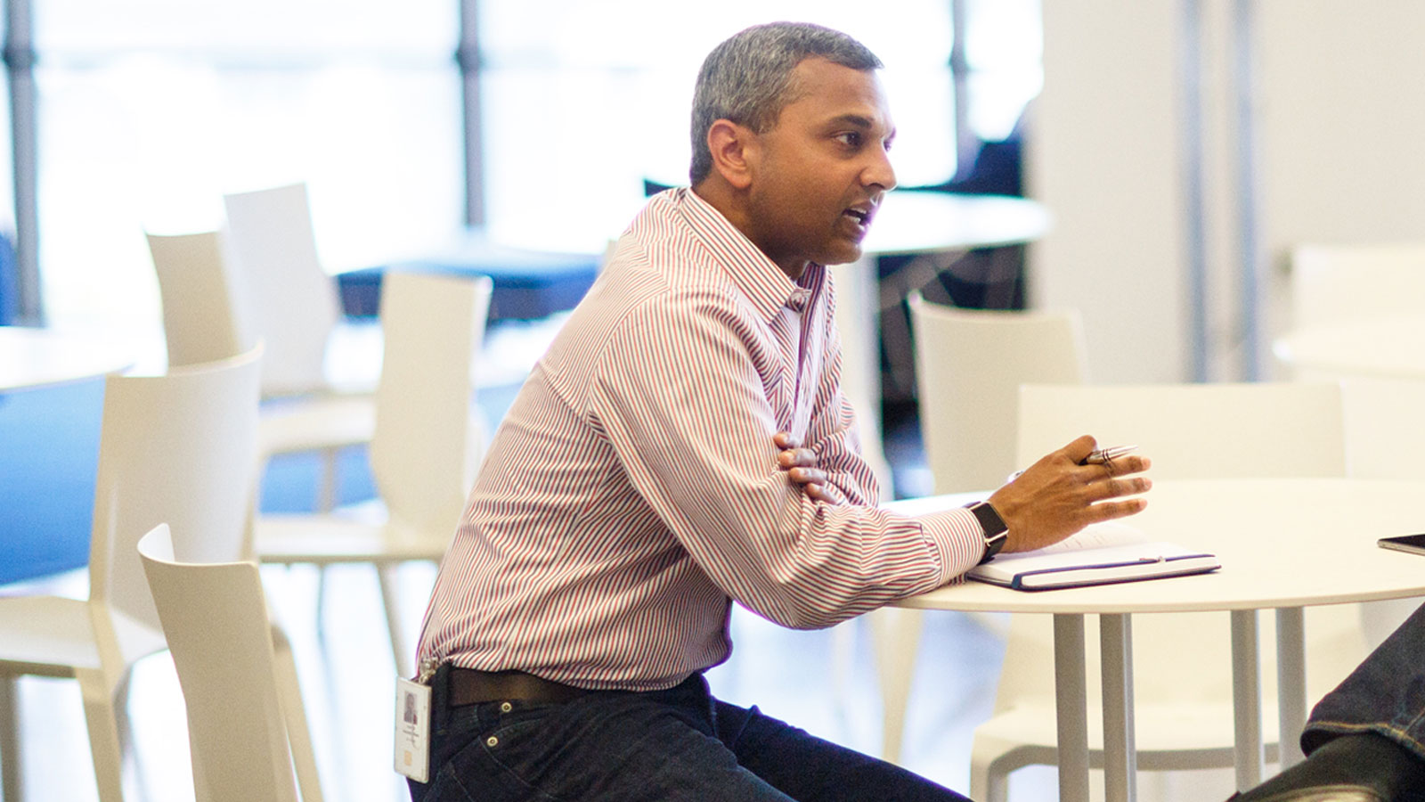 A man sitting at a desk who is having conversation with others.