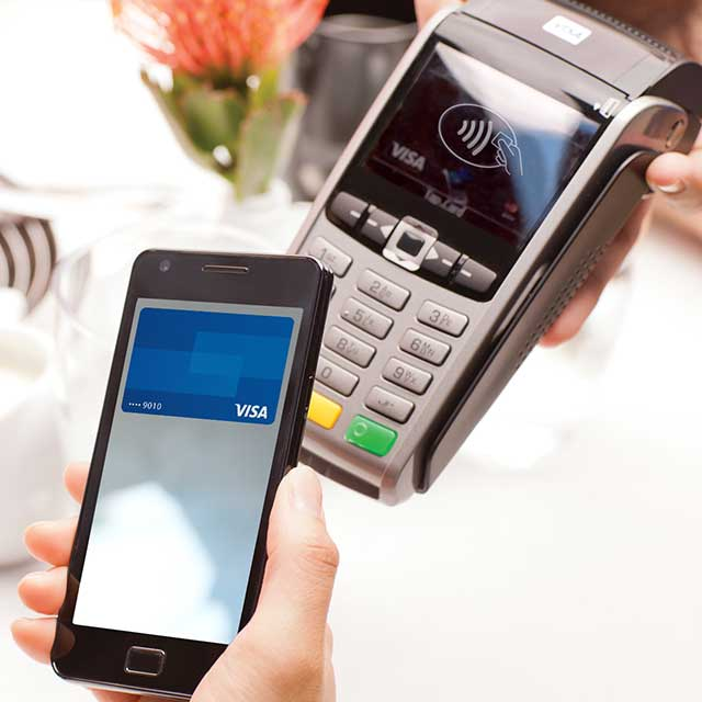 A mobile phone being held over a checkout terminal displaying the Contactless Symbol.
